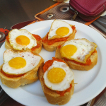 Tostada con tomate, topped with a fried egg for a substantial breakfast or snack